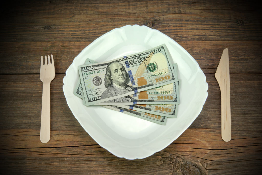 White Ceramic Plate With USA New One Hundred Dollar Bills, Wooden Fork And Knife On Rough Wood Background Or Texture