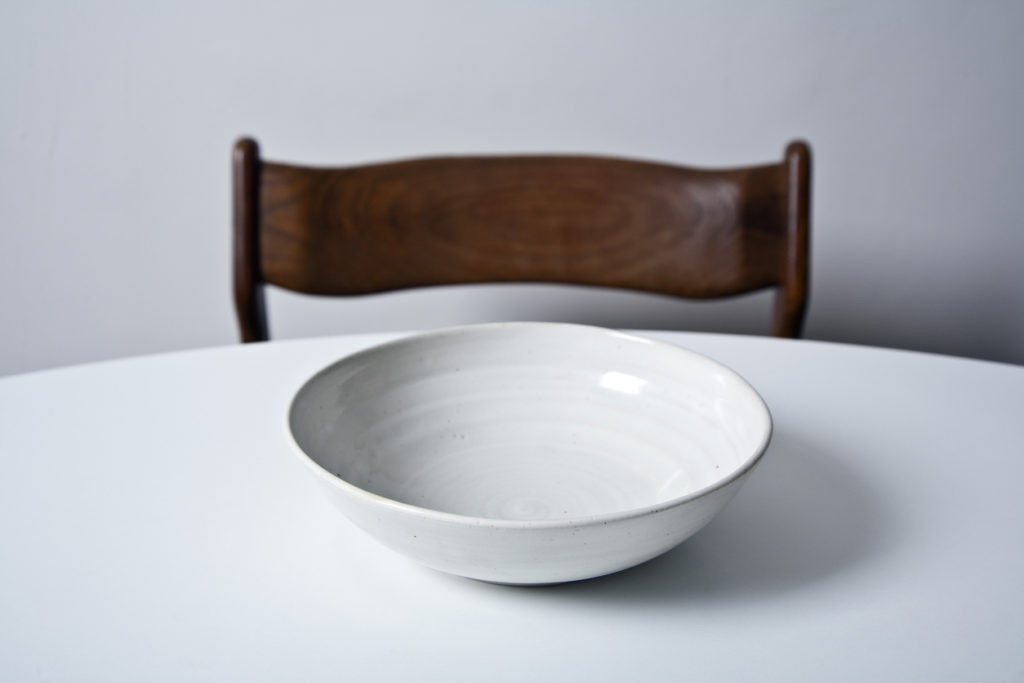 White bowl on the wooden board